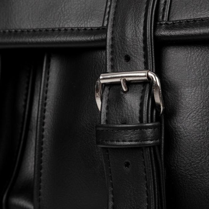 Metalowe klamry zapinające klapę torby.
