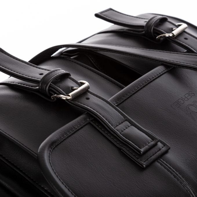 Dwa uchwyty z metalowymi sprzączkami które zapinają klapę torby